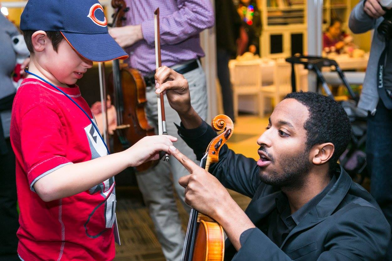 Kyle Dickson coaches a young violinist