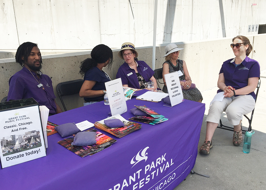 Grant Park Music Festival volunteers and docents gather at the welcome tent